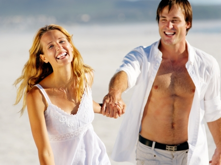 stress free: romantic honeymoon couple walk on the beach during a tropical summer holiday vacation. carefree stress free lifestyle concept.