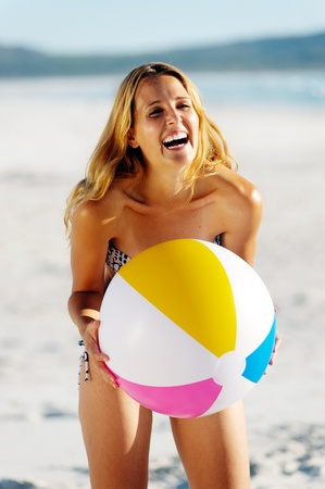 healthy young woman laughing with beachball while on the beach in summer photo