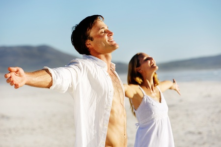 free standing: Young stress free couple enjoy the summer sun on the beach. Arms out, heads back and carefree attitudes. Stock Photo