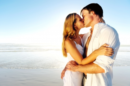 Newlywed couple kissing on honeymoon, beach vacation in summer and an intimate moment.