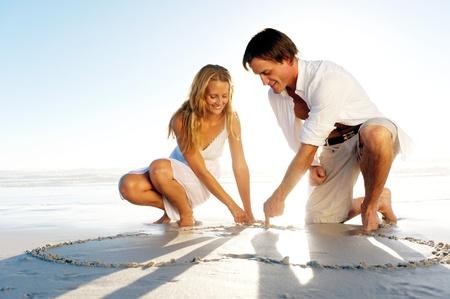 ひざまずく: ロマンチックな若いカップルの新婚旅行に砂で心臓の形を描画します。夏のビーチの愛の概念。 写真素材