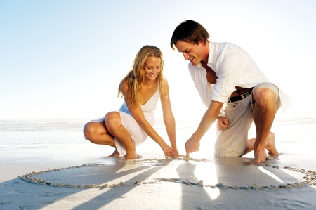 kneeling woman: Romantic young couple draw heart shapes in the sand while on honeymoon. summer beach love concept.