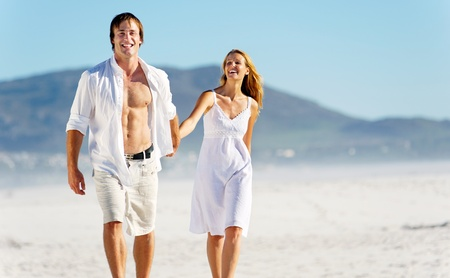 laughing couple: romantic honeymoon couple walk on the beach during a tropical summer holiday vacation. carefree stress free lifestyle concept.
