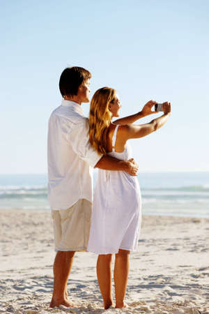 Summer beach honeymoon couple standind on the sand and taking pictures of the beautiful sunset over the ocean photo