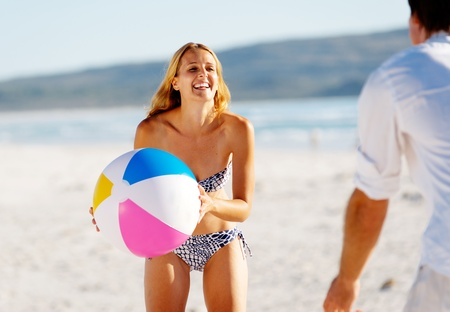 Young couple on a summer beach vacation playing with a beachball and having carefree fun photo