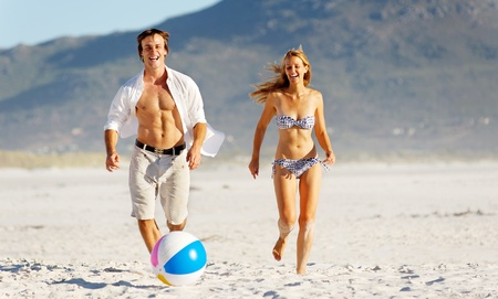 guy on beach: Summer beach couple playing with a beach ball on the sand, laughing and enjoyng the sunshine outdoors