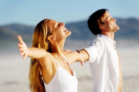 Jong stress paar genieten van de zomerzon op het strand. Armen, hoofden terug en zorgeloos attitudes.