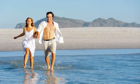 Summer beach love couple run through the shallow water splashing and having fun together. laughing and smiling carefree concept. photo