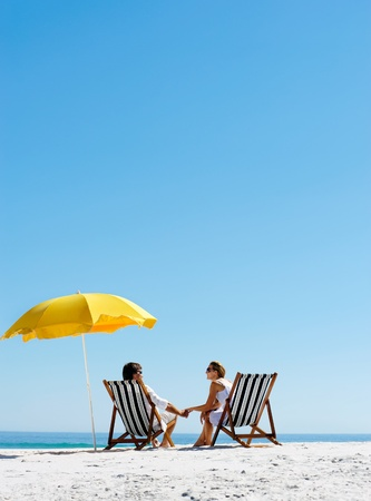 honeymoon couple: Beach summer couple on island vacation holiday relax in the sun on their deck chairs under a yellow umbrella. Idyllic travel background. Stock Photo