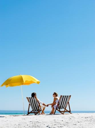 luna de miel: Pareja de verano en la playa de vacaciones vacaciones en la isla relajarse bajo el sol en sus sillas de cubierta bajo un paraguas amarillo. Antecedentes de viaje id�lico. Foto de archivo