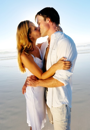 Newlywed couple kissing on honeymoon, beach vacation in summer and an intimate moment. Stock Photo