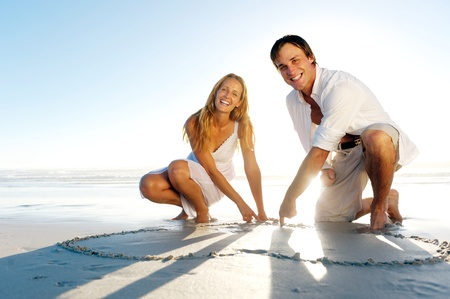 Romantic young couple draw heart shapes in the sand while on honeymoon. summer beach love concept. photo