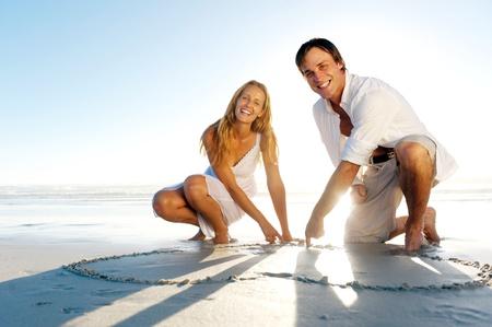 háttérvilágítású: Romantikus fiatal pár felhívni szív alakú a homokban, míg a nászútra. nyári strand szerelem fogalom.