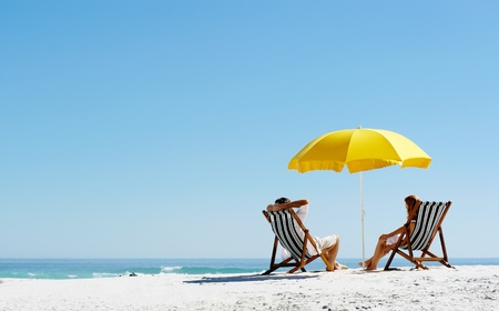 guy on beach: Beach summer couple on island vacation holiday relax in the sun on their deck chairs under a yellow umbrella. Idyllic travel background. Stock Photo