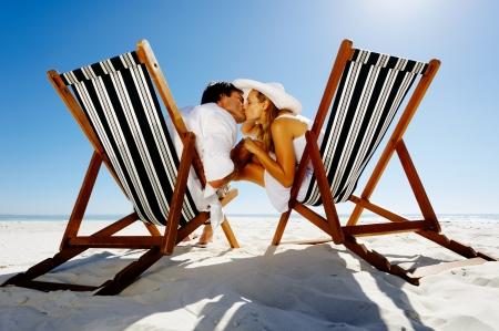 luna de miel: Pareja de verano la playa besando sentados en sillas de playa disfrutando de un momento �ntimo