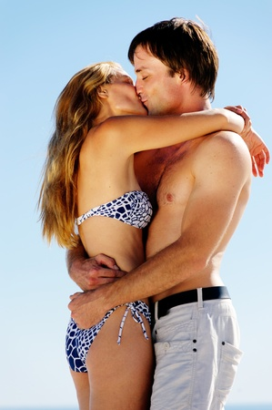 kissing summer beach couple on vacation in a tropical island scene photo