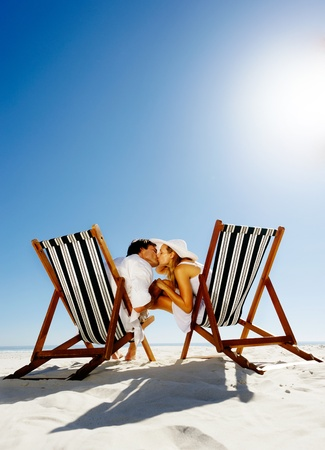 Summer beach kissing couple sitting on deck chairs enjoying an intimate moment photo