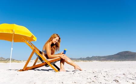 美丽的年轻女子在她的腿上涂防晒霜,而坐在海滩在夏天。