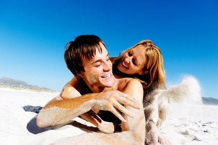 affectionate young couple enjoy a summer beach vacation and throw sand all over each others faces.
