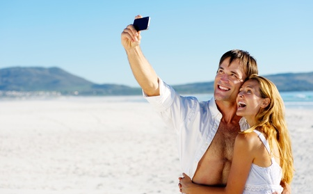 young couple pose for a self portrait at the beach, laughing and having summer fun together photo