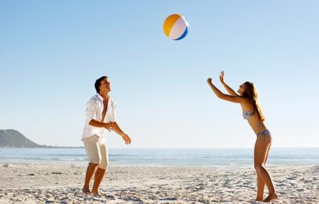 coger: Pareja joven en unas vacaciones de verano en la playa jugando con una pelota de playa y divertirse sin preocupaciones