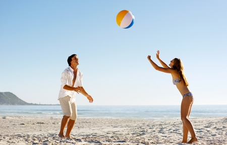 play ball: Young couple on a summer beach vacation playing with a beachball and having carefree fun