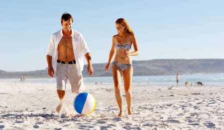 Summer beach couple playing with a beach ball on the sand, laughing and enjoyng the sunshine outdoors photo