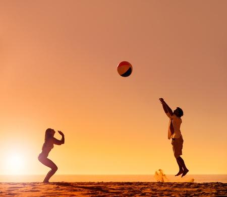 beach ball girl: Verano de pelota de playa silueta de pareja puesta de sol en la arena se divierten