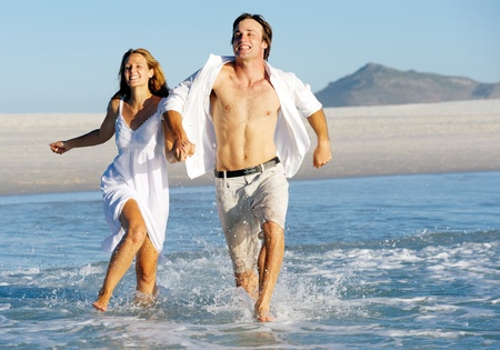 having fun: Summer beach love couple run through the shallow water splashing and having fun together. laughing and smiling carefree concept.