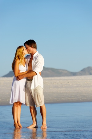 Couple in love stand on the beach in summer and share a kiss at sunset alone and on honeymoon. Stock Photo - 12755063