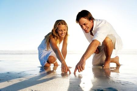 arrodillarse: Rom�ntico joven pareja formas Dibuje un coraz�n en la arena, mientras que en luna de miel. concepto de la playa del verano el amor. Foto de archivo