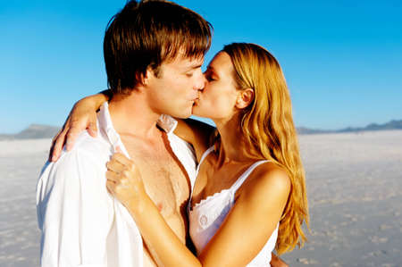 Newlywed couple kissing on honeymoon, beach vacation in summer and an intimate moment. photo