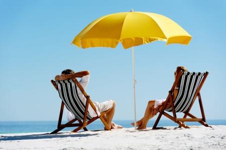 島休暇にビーチの夏のカップル黄色い傘の下で彼らのデッキチェアで日光浴でおくつろぎください。牧歌的な旅行の背景。