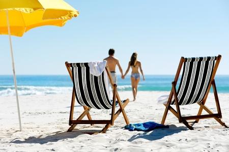 strandstoel: Tropische zomer strand vakantie paar lopen naar de oceaan hand in hand terwijl hij op huwelijksreis vakantie