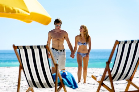 bikini couple: tropical island vacation summer beach couple walking holding hands and laughing together in the sun