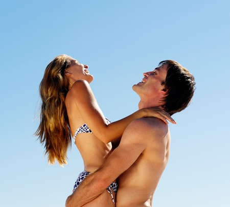 embracing summer beach couple hugging and laughing together on a tropical island photo