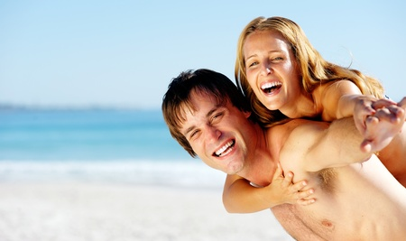 carefree couple embrace and enjoy some summer beach loving on a tropical island photo