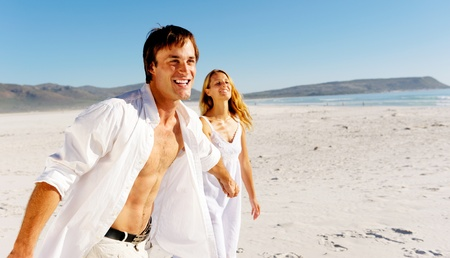 romantic honeymoon couple walk on the beach during a tropical summer holiday vacation. carefree stress free lifestyle concept. Stock Photo - 12753567