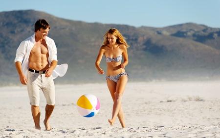 Sommer-Strand Paar spielt mit einem Wasserball auf dem Sand, Lachen und Sonnenschein im Freien die enjoyng