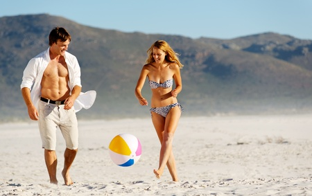 vitality: Summer beach couple playing with a beach ball on the sand, laughing and enjoyng the sunshine outdoors