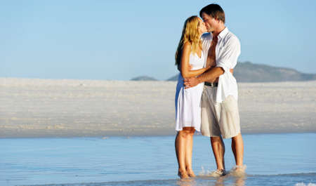 beach kiss: Couple in love stand on the beach in summer and share a kiss at sunset alone and on honeymoon. Stock Photo