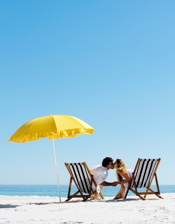 beach kiss: Beach summer couple kissing on island vacation holiday in the sun on their deck chairs under a yellow umbrella. Idyllic travel background.