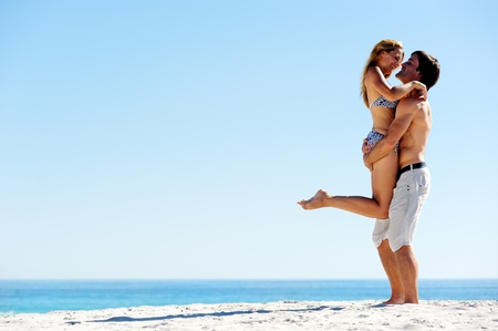 embracing summer beach couple hugging and laughing together on a tropical island