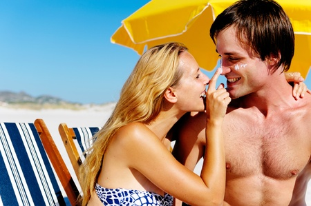 skin protection: Summer beach couple take care of their skin with sunblock lotion of high SPF for maximum protection