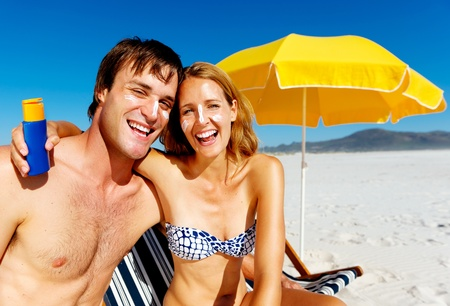 suncare couple on a summer beach vacation have good skincare with high spf sunblock photo