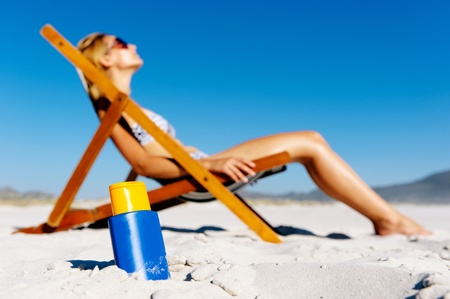 Attractive woman sunbathing alone during summer on the beach with high spf sunblock Imagens