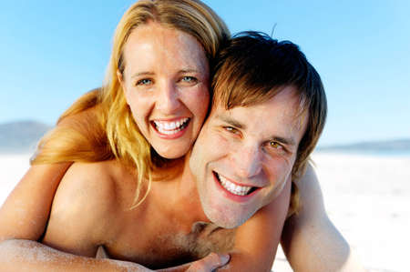 affectionate young couple enjoy a summer beach vacation and throw sand all over each others faces. photo