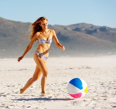 girl kick: summer beach bikini girl with beachball laughing and having fun
