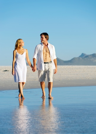 Young couple in love holding hands and taking a romantic walk along the beach during summer photo