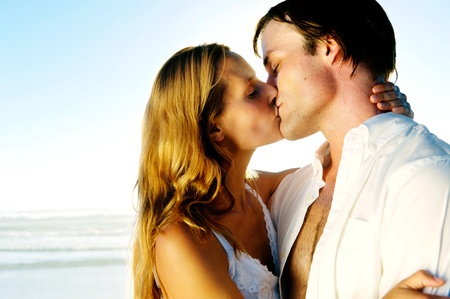 sexy couple embrace: Newlywed couple kissing on honeymoon, beach vacation in summer and an intimate moment. Stock Photo